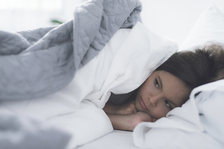 A little black girl lies in a white bed under a white blanket and frowns