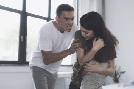 女性は彼女の夫が怒って夫をつかまえたので、彼女の幼い娘を畏敬の目で抱きしめた
