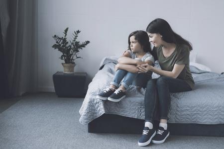 De moeder omhelst haar dochter, die naast haar op het bed zit met haar armen om haar benen en frons opzij Stockfoto