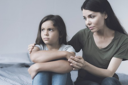 The mother tries to comfort her daughter, who sits next to her and looks indifferently
