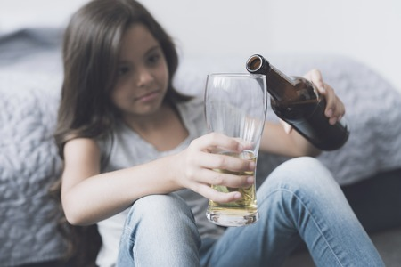 The dark-haired girl sits near the bed and pours herself a beer in a glass Stock Photo