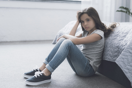 A small dark-haired girl sits on the floor leaning on the bed and propping her head with her hand Stock Photo