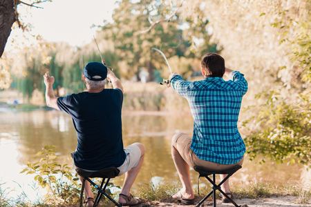 An old man in a black T-shirt and a man in a blue shirt are sitting on the bank of the river on folding chairs and fishing with spinnings.