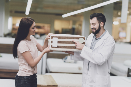 Consultant-orthopedist helps the girl to choose a mattress in the store. He offers her a mattress and shows his sample
