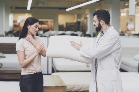 Orthopedic consultant helps a woman choose an orthopedic pillow. He shows her one of the pillow options Banco de Imagens