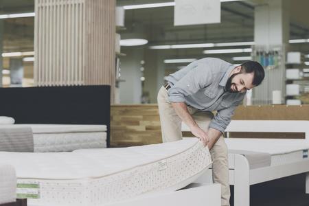 Een man inspecteert een matras in een matraswinkel. Hij tilde een van hen op