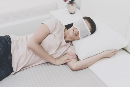 The woman put on a blindfold on her eyes and fell asleep on the bed in the store
