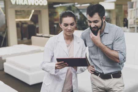 An orthopedist woman advises a man in a mattress and bed store