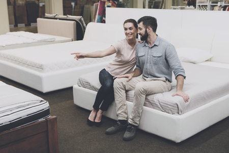 A couple is sitting on the bed, in a bed shop. They are happy