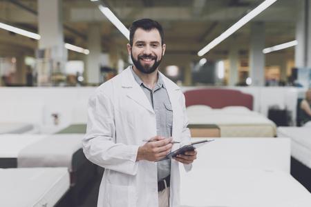 ベッドの大きな店の背景に対して男性の整形外科のポーズ。彼は手にタブレットを持ち、彼を見ています。