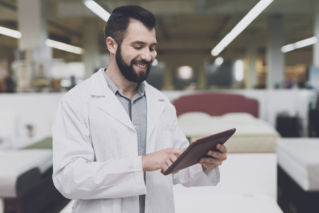 Interior room: A male orthopedic pose against the background of a large store of beds. He holds tablet in his hands and looks at him.