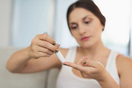 A pregnant woman sits at home on a light sofa. She holds a sugar level analyzer in her hands and makes herself a prick in her finger to take a blood sample