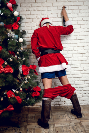 Dronken Santa Claus urineert onder de nieuwjaarsboom na een tumultueus feestje. Hij staat nauwelijks op. naast een prachtige kerstboom.