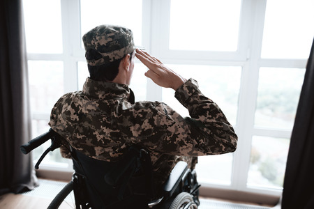 The disabled in military uniform sits in a wheelchair. He looks out the window and salutes. In front of him is a large panoramic window. He is in his modern apartment. Zdjęcie Seryjne