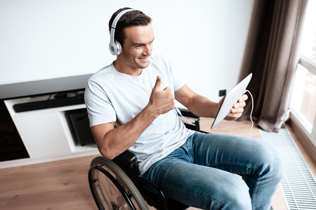 A disabled person in a wheelchair sits in front of a large panoramic window and communicates via video through his tablet. He has headphones on his head. He is in his large modern apartment. Stock Photo