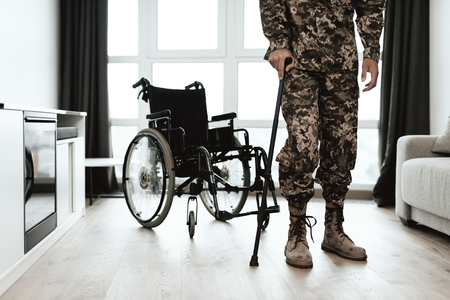 A disabled soldier is leaning on a crutch. He got up from the wheelchair and goes. Behind him is a wheelchair. He is standing in a large spacious living room.