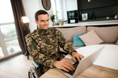 Disabled in military uniform, he works for his laptop. He sits at his desk. He is in his large modern apartment.
