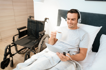 The invalid lies in bed and looks something on the tablet. He smiles. because he is happy. Next to his bed is his black wheelchair. It lies on a large white step.