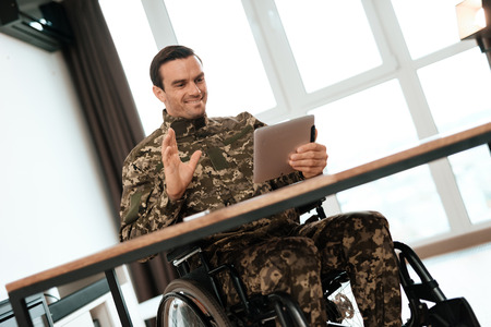 The disabled in military uniform sits at the table and works with the tablet. Behind it is a large panoramic window. He is in his large modern apartment.
