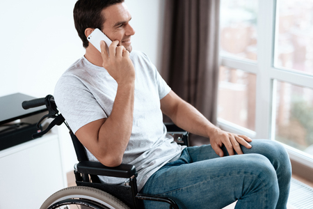 The disabled person sits in a wheelchair in front of a large panoramic window. He is talking to someone on his smartphone. He is in his large bright living room. He smiles. Zdjęcie Seryjne