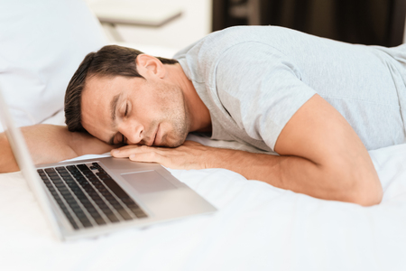 breackfast: The man fell asleep on the bed before the laptop was turned on and open. He wears a gray T-shirt. He fell asleep on the big white bed.