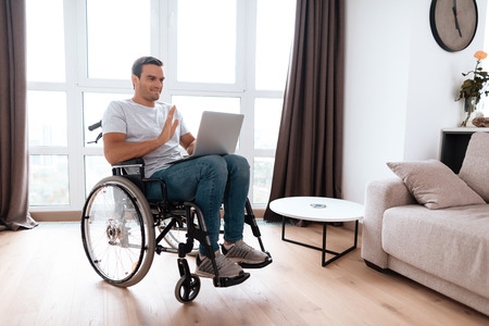 The disabled person sits in a wheelchair in front of a large panoramic window. He has a laptop on his lap, for which he works. He is in his large bright living room.