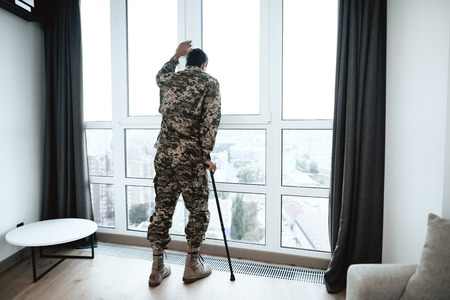 A disabled soldier stands with his hand on the window. He feels sad and depressed. It stands near a large panoramic window, from which you can see the city. Banco de Imagens