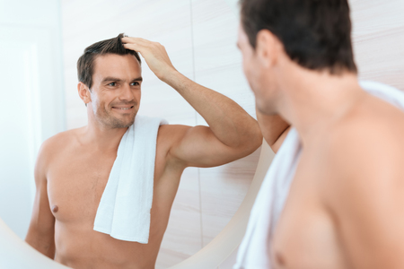 A man stands in the bathroom in the morning and looks at himself in the mirror. He smiles. He had just taken a refreshing shower and was glad of it.