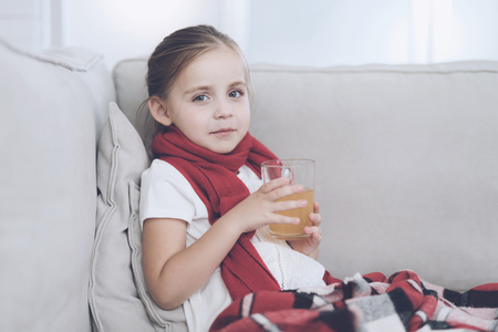 Little sick girl sits on a white couch wrapped in a red scarf. She is sitting with a cup of medicinal tea Reklamní fotografie - 92325102