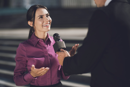 A woman with a smile on her face answers the question. A man holds a microphone listening to an answer