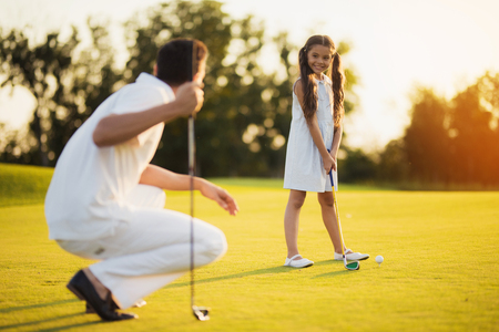 The father squats with a golf club in his hand and looks at his daughter, who looks at him and prepares to hit the ball Фото со стока