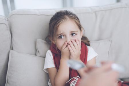 작은 아픈 소녀 빨간색 스카프에 싸여 흰 소파에 앉는 다. 그녀는 그녀에게 주어진 시럽을 먹고 싶지 않습니다. 스톡 콘텐츠