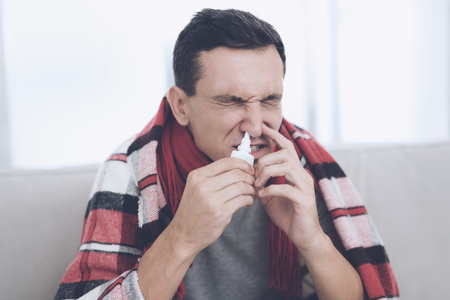 A man with a cold sits on the couch, hiding behind a red rug. He sprinkles nasal spray into his nose Stock Photo - 89814857