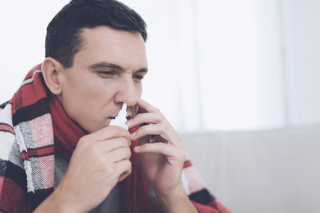 A man with a cold sits on the couch, hiding behind a red rug. He sprinkles nasal spray into his nose