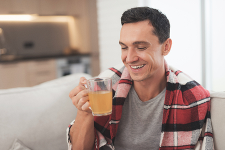 A man with a cold sits on the couch, hiding behind a red rug. He drinks medicinal tea Stock Photo
