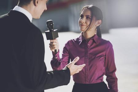 Un giornalista in una camicia di Borgogna sorridente ascolta la risposta di allarme