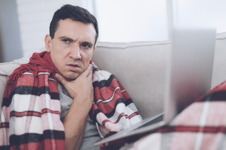 A man with a cold sits on the couch, hiding behind a red rug. He is sitting with his laptop on his lap