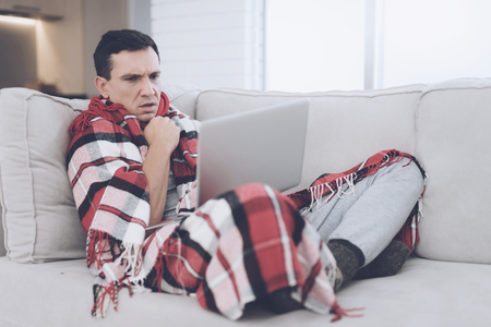 A man with a cold sits on the couch, hiding behind a red rug. He is sitting with his laptop on his lap Stock Photo - 89826604