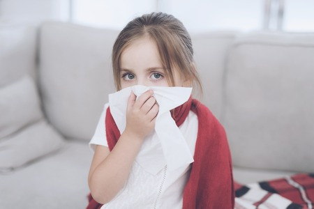Little sick girl sits on a white couch wrapped in a red scarf. She blows her nose into a napkin Stock Photo - 89856885