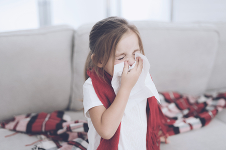 Little sick girl sits on a white couch wrapped in a red scarf. She blows her nose into a napkin Stock Photo - 92325167
