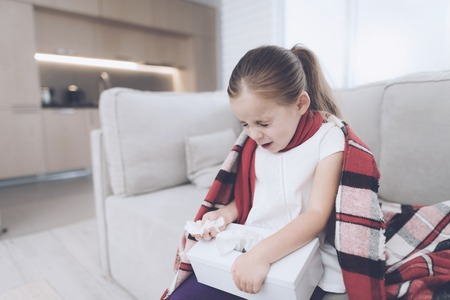 Little sick girl sits on a white couch wrapped in a red scarf. She sneezes, taking out a napkin Stock Photo