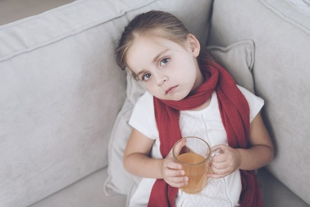 Little sick girl sits on a white couch wrapped in a red scarf. She is sitting with a cup of medicinal tea Stock Photo - 89826607