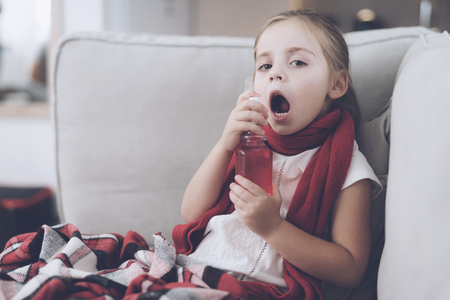 Little sick girl sits on a white couch wrapped in a red scarf. She splashes her throat with a medicinal spray