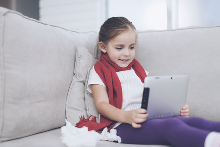 Little sick girl sits on a white couch wrapped in a red scarf. She holds a gray tablet in her hands