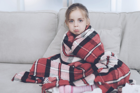 Little sick girl sits on a white couch wrapped in a red scarf. She is cold and she wrapped herself in a red blanket Stock Photo - 92325175