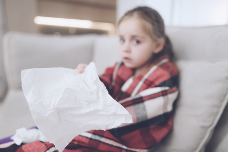 Little sick girl sits on a white couch wrapped in a red scarf. She holds a napkin in front of the camera Stock Photo
