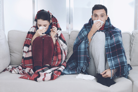 The couple is sitting on the couch wrapped in blankets. Man and woman are sick. The man flies out. The woman, too