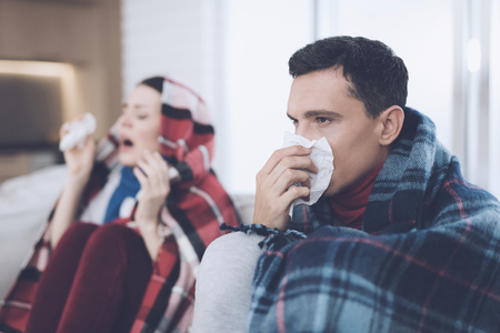 The couple is sitting on the couch wrapped in blankets. Man and woman are sick. The man flies out. Woman sneezing Stock Photo - 92325179