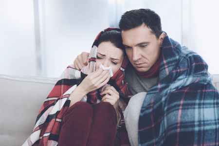 The couple is sitting on the couch wrapped in blankets. Man and woman are sick. A man hugs a woman who flies Stock Photo - 89857107