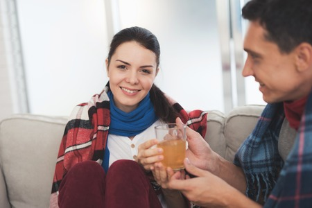 The couple is sitting on the couch wrapped in blankets. Man and woman are sick. A man gives a woman a cup of healing tea Stock Photo